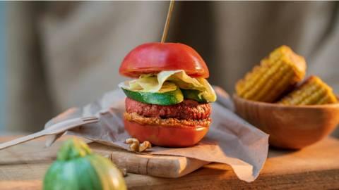 Вегански бургер в печен домат с грилована тиквичка, чушково песто със сушени домати и билки и гарнитура от печена царевица