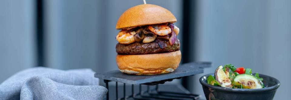 Бургер от говеждо със сирене Чедър и скариди, поднесен със свежа салата с печени тиквички, чери домати, рукола и ментов дресинг