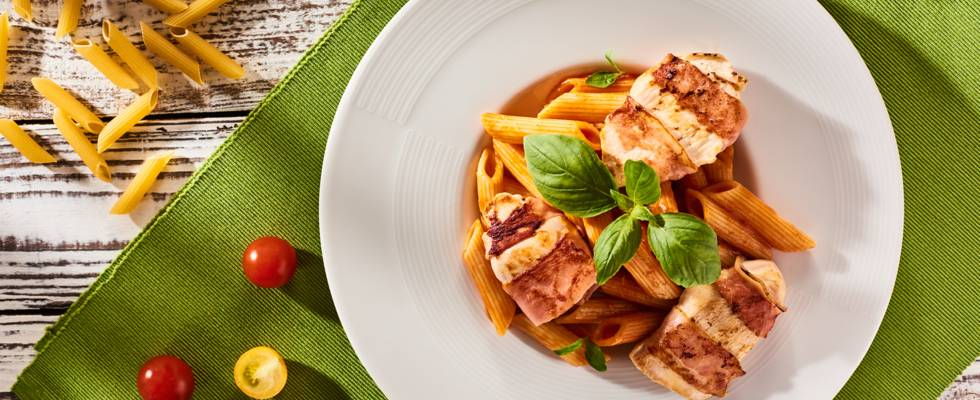 Пилешко филе с коричка от бекон, гарнирано с паста пене с пресни домати